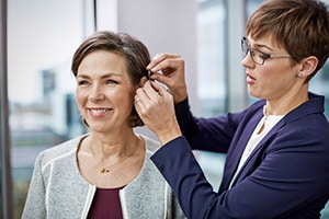 Audiologist Fitting a Hearing Aid to a Patient