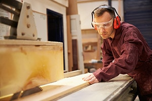 Man with hearing protection using a table saw