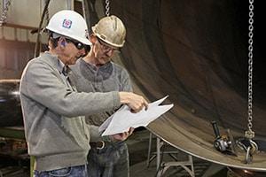 Two men on a job site wearing ear plugs